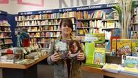 Ein Mädchen zeigt seine beiden ausgewählten Bücher