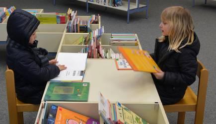 Zwei Kinder sitzen sich gegenüber und schauen sich Bücher an