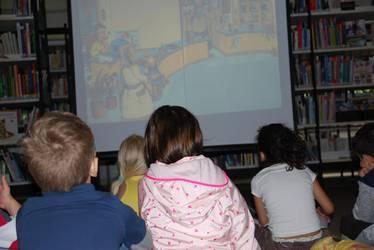 KInder sitzen vor einer Leinwand in der Bücherei