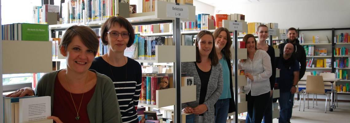 Die Mitarbeiter/innen der Bücherei stehen zwischen den Bücherregalen