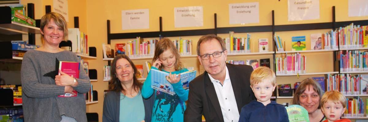 Jürgen Köhne in der Mitte mit Kindern, Eltern und Mitarbeiterinnen der Bibliothek vor der Elternbibliothek
