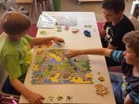 Eine Gruppe Kinder spielt das Brettspiel Kingdom Builder