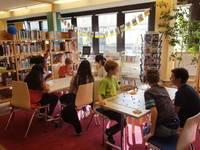 An zwei Tischen werden verschiedene Brettspiele wie z.B. Kingdom Builder gespielt