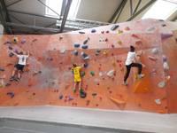 Kinder klettern an Griffen die Wände hinauf