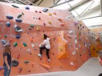 Ein Kind klettert mithilfe der Griffe die Wand hinauf