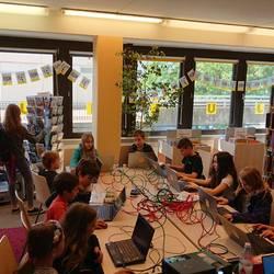 Kinder sitzen um einen Tisch und bauen an Laptops Welten in Minecraft