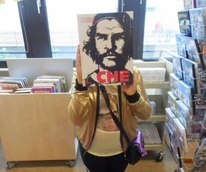 Ein Kind hält sich ein Buch mit dem Kopf von Che Guevara auf dem Cover vor das Gesicht