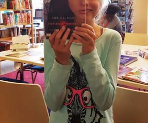 Die Gesichtshälfte eines Mädchens wird von einem Buchcover verdeckt, dass ein halbes Frauengesicht zeigt