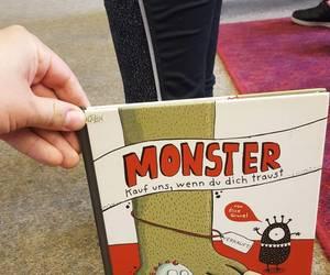 Ein Buchcover mit einem Monsterbein darauf wird vor ein Kinderbein gehalten