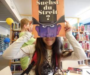 Ein Mädchen hält sich ein Buch mit einem Cowboykopf auf dem Cover vor das Gesicht