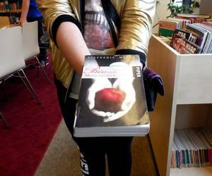 Die Hände eines Kindes verschwinden hinter einem Buchcover mit Händen die einen Apfel halten darauf