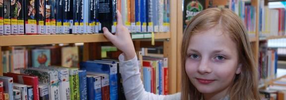 Eine junge Leserin bei der Auswahl eines Buches