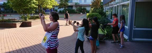 Die Teilnehmerinnen stehen mit Kameras vor dem Rathaus und suchen Motive