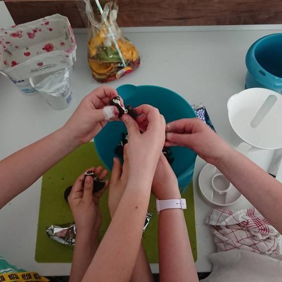 Kinder bröseln Kekse in eine Rührschüssel