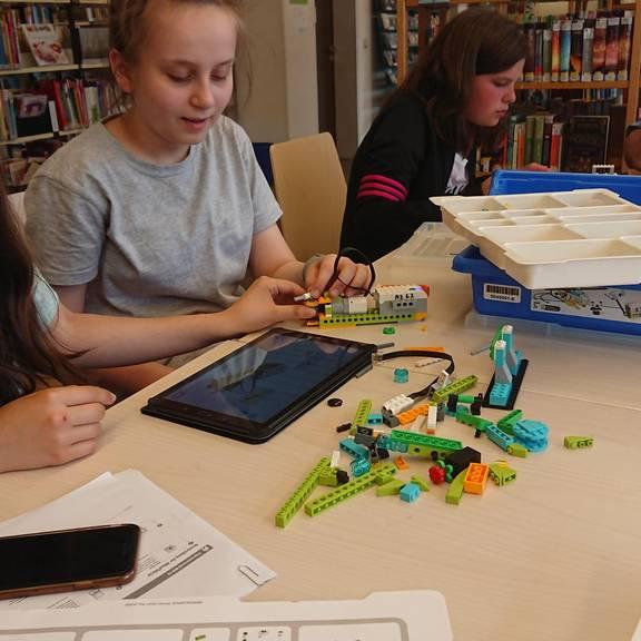 Kinder bauen Roboter aus  Lego-Steinen