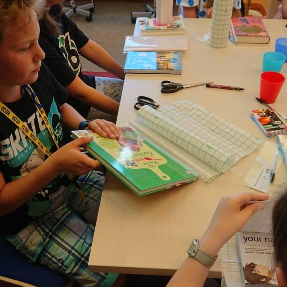 Kinder bearbeiten ihre für die Bücherei ausgesuchten Bücher