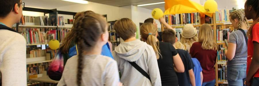 Eine Reighe von Kindern, bilden eine Schlange vor einem Bücherregal