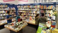Die Kinder suchen sich in der Buchhandlung ihre Wunschtitel aus