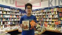 Ein Junge zeigt seine beiden ausgewählten Bücher