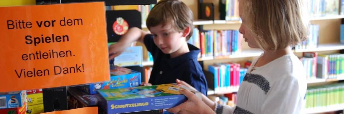 Ein Junge und ein Mädchen prüfen das Spiele-Angebot und stehen vor einem Regal