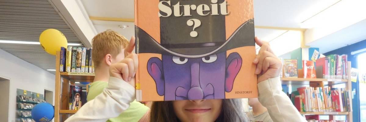 Mädchen hält sich ein Buch vor das Gesicht, so dass es aussieht, als habe sie das auf dem Titel abgebildete Gesicht