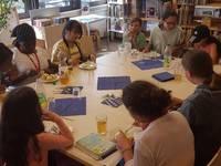 Die Kinder sitzen zusammen am Tisch, essen ihre Waffeln und sprechen über Bücher
