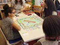 An zwei Tischen werden verschiedene Brettspiele wie z.B. Monopoly gespielt