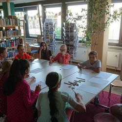 Kinder sitzen mit einer Comiczeichnerin am Tisch