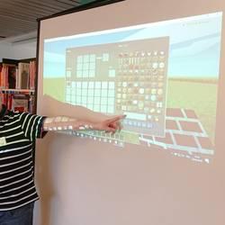 Ein Mitarbeiter des Multimediamobils zeigt die Funktionen von Minecraft auf einer Leinwand