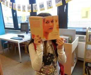 Ein Mädchen hält sich ein Buch mit einem Frauenkopf auf dem Cover vor das Gesicht