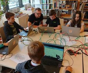 Ein Mitarbeiter des Multimediamobils leitet die Kinder in Minecraft an