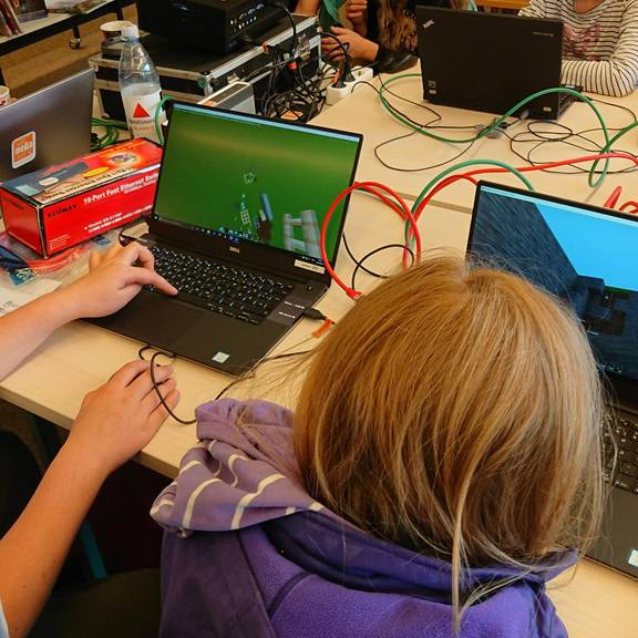 Kinder sitzen an Laptops und bauen Welten in Minecraft