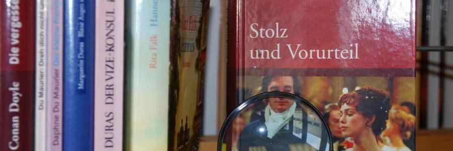 Bücher in Großdruck mit einer Lupe im Vordergrund