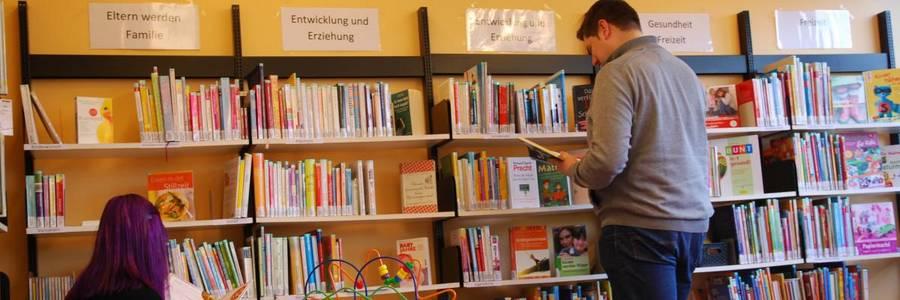 Bücherregale der Elternbibliothek mit zwei Nutzenden vor den Regalen und Kinderbücher im Vordergrund